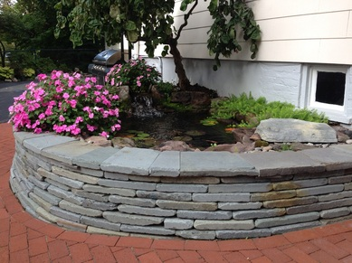 Landscape Design, water feature, stack stone wall with landscape lighting in Rochester, (NY) by Acorn Ponds & Waterfalls- Landscape ideas for your outdoor living. Image