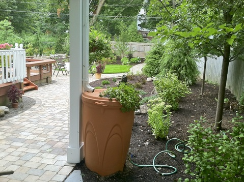 Landscape Design With Paver Patio, Water Features, Landscape Lighting, Rain Barrel & New Plantings in Rochester NY By Acorn Ponds & Waterfalls - Contact us now to get started on your escape! Image