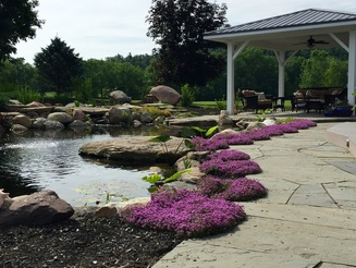 Blue stone patio & landscape design with recreational pond installation in Rochester New York (NY) by Acorn Ponds & Waterfalls